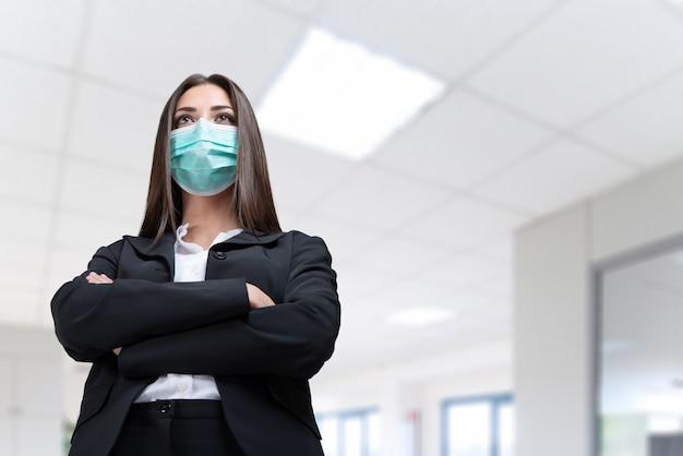 Młoda zamaskowana bizneswoman w jej koncepcji biura, koronawirusa i pracy