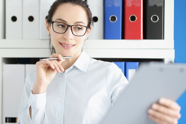 Młoda zamyślona bizneswoman w okularach studiuje dokumenty finansowe