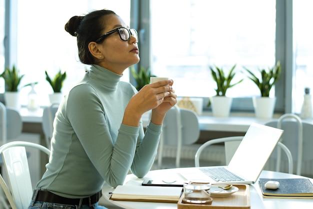 Młoda zamyślona kobieta freelancer w casualwear i okularach po filiżance herbaty przy przerwie przy stole w kawiarni