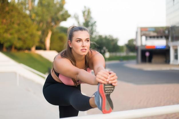 Młoda zamyślona kobieta w rozmiarze plus size w sportowej bluzce i leginsach, rozciągnięta w zamyśleniu, patrząc na bok, spędzając czas na świeżym powietrzu