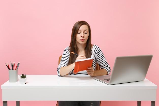 Młoda zamyślona kobieta w zwykłych ubraniach pisząca notatki na notebooku siedzącym i pracującym przy białym biurku ze współczesnym laptopem na pc