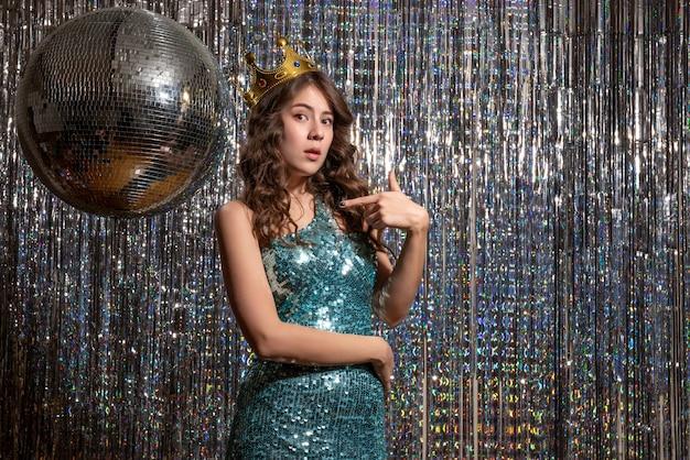 Młoda zamyślona piękna pani ubrana w niebiesko-zieloną błyszczącą sukienkę z cekinami z koroną i wskazująca na przyjęcie
