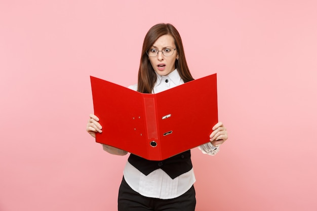 Młoda zaniepokojona kobieta biznesu w okularach trzyma patrząc na czerwony folder na dokument dokumentów na białym tle na pastelowym różowym tle. szefowa. koncepcja bogactwa kariery osiągnięcia. skopiuj miejsce na reklamę.