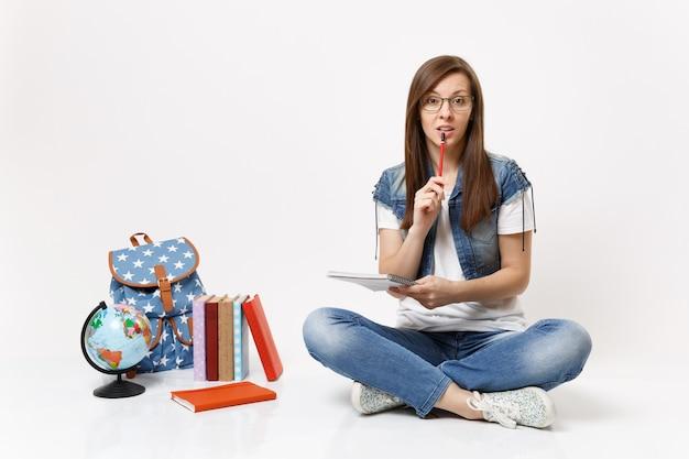 Młoda zaniepokojona zamyślona studentka w okularach trzymająca ołówek w pobliżu ust, trzymająca notatnik siedząca w pobliżu globusowego plecaka na białym tle