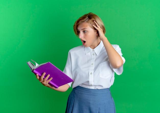 Młoda zaskoczona blondynka rosjanka kładzie rękę na głowie patrząc na książkę na białym tle na zielonym tle z miejsca kopiowania