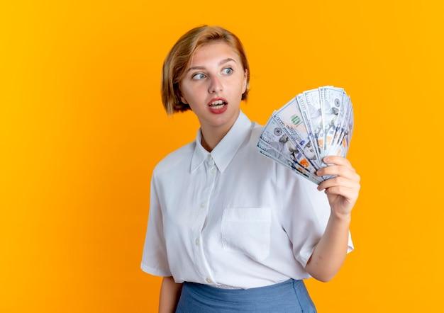 Młoda zaskoczona blondynka rosjanka trzyma i patrzy na pieniądze na białym tle na pomarańczowym tle z miejsca na kopię