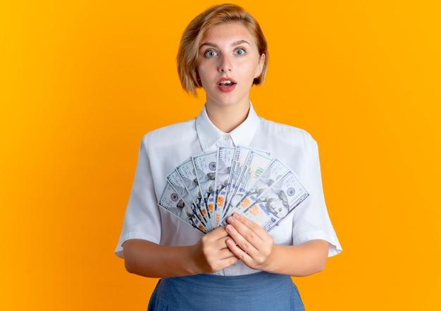 Młoda zaskoczona blondynka rosjanka trzyma pieniądze na białym tle na pomarańczowym tle z miejsca na kopię