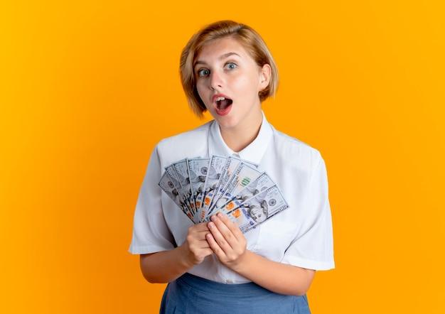 Młoda zaskoczona blondynka rosjanka trzyma pieniądze patrząc na kamery na białym tle na pomarańczowym tle z miejsca na kopię