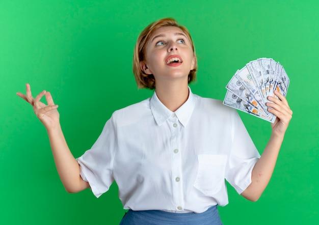 Młoda zaskoczona blondynka rosjanka trzyma pieniądze patrząc z podniesioną ręką