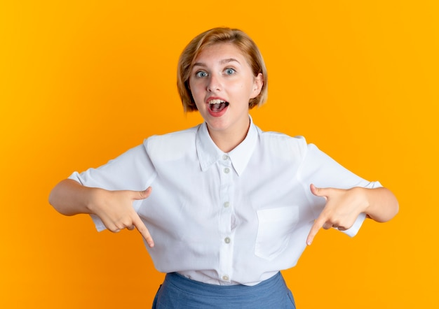 Młoda zaskoczona blondynka rosjanka wskazuje w dół na białym tle na pomarańczowym tle z miejsca na kopię