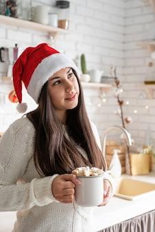 Młoda zaskoczona brunetka kobieta w kapeluszu santa