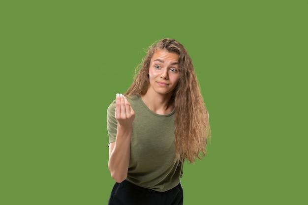 Młoda zaskoczona kobieta przeciw zielonej ścianie