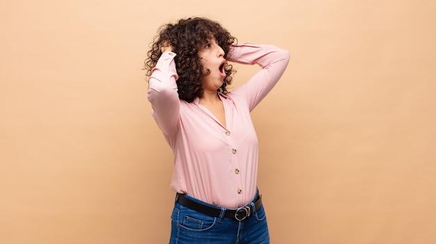 Młoda zaskoczona kobieta z kręconymi włosami i różową koszulą
