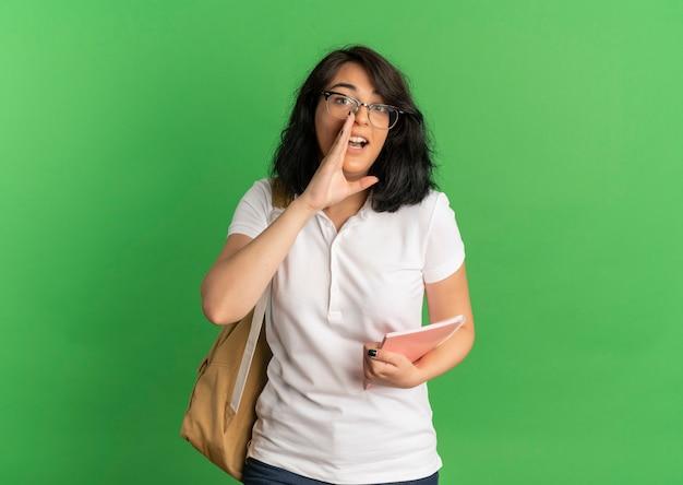 Młoda, zaskoczona, ładna uczennica kaukaska w okularach i torbie udaje, że dzwoni do kogoś ręką trzymającą notes na zielono z miejscem na kopię