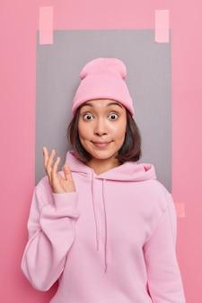 Młoda zaskoczona młoda azjatka patrzy wyłupiastymi oczami, trzyma rękę podniesioną z oburzeniem, nosi swobodną bluzę i kapelusz pozuje na różowym tle z pustą pustą przestrzenią na twoją reklamę