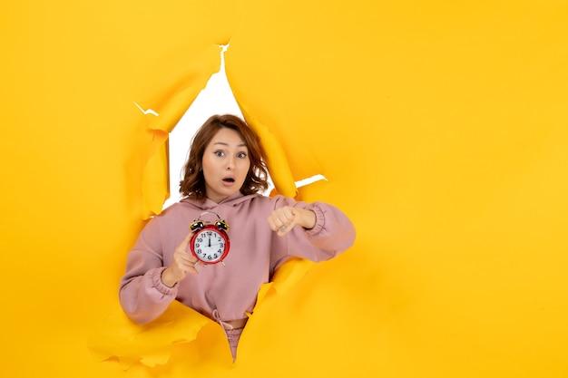 Młoda zaskoczona piękna dama trzyma zegar i sprawdza swój czas na żółtym rozdartym przełomowym tle