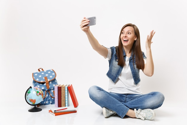 Młoda zaskoczona studentka robi selfie zastrzelona na telefonie komórkowym i rozkłada ręce w pobliżu kuli ziemskiej, plecaka, podręczników szkolnych na białym tle