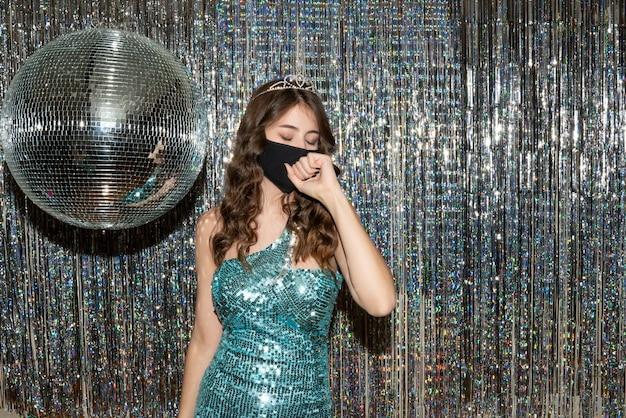 Młoda zastanawiająca się ładna dziewczyna ubrana w błyszczącą sukienkę z cekinami z koroną w czarnej masce medycznej na przyjęciu