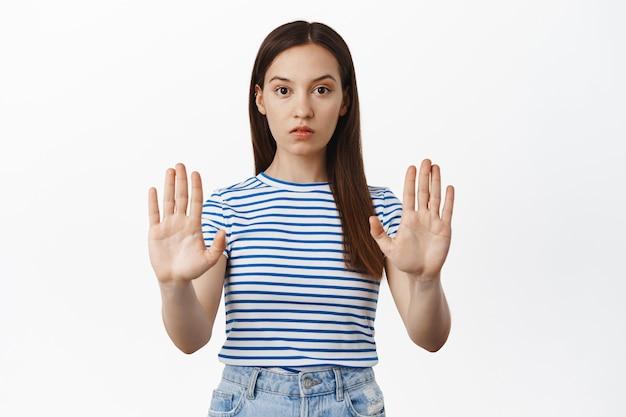 Młoda zatroskana kobieta wyciąga ręce, wyciąga dłonie w tabu, nie blokuje gestu, odmawia czegoś, nie akceptuje i zabrania działania, stoi przy białej ścianie