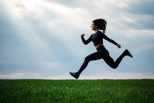Młoda zawodowa gimnastyczka skacze w przyrodzie na tle błękitnego nieba. sportowiec w czarnym topie i czarnych legginsach wykonuje ćwiczenia akrobatyczne