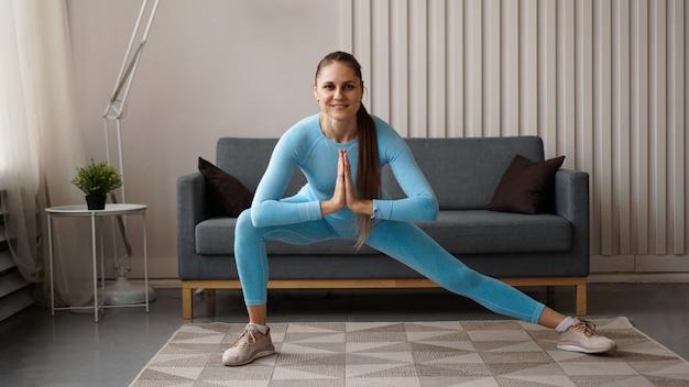 Młoda zdecydowana pewnie szczupła kobieta robi ćwiczenia w domu. trener fitness trenuje w domu podczas kwarantanny. jasne nowoczesne wnętrze