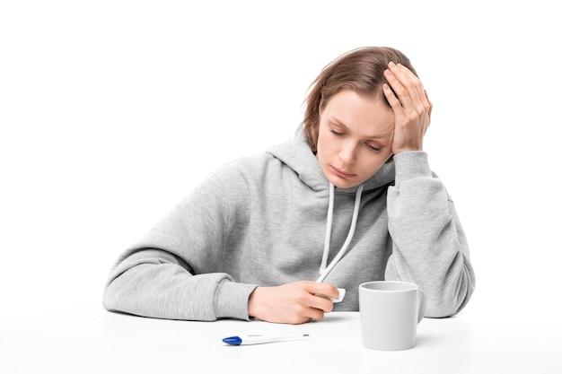 Młoda zdenerwowana chora kobieta w bluzie z kapturem siedzi przy biurku, mierzy temperaturę i przyjmuje leki podczas pobytu w domu