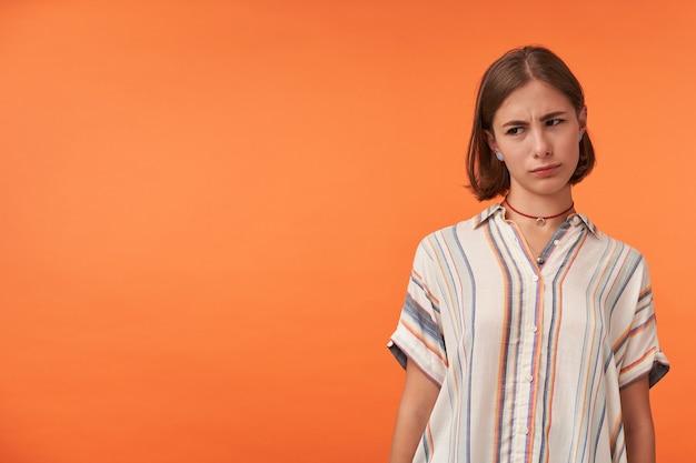 Młoda zdenerwowana dziewczyna z naszyjnikiem na sobie pasiastą koszulę.
