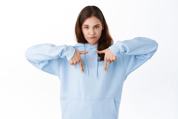 Młoda zdenerwowana dziewczyna z ponurą smutną twarzą, wskazując palcami na dole miejsce kopiowania, narzekająca na niesprawiedliwą sytuację, stojąca niezadowolona przy białej ścianie