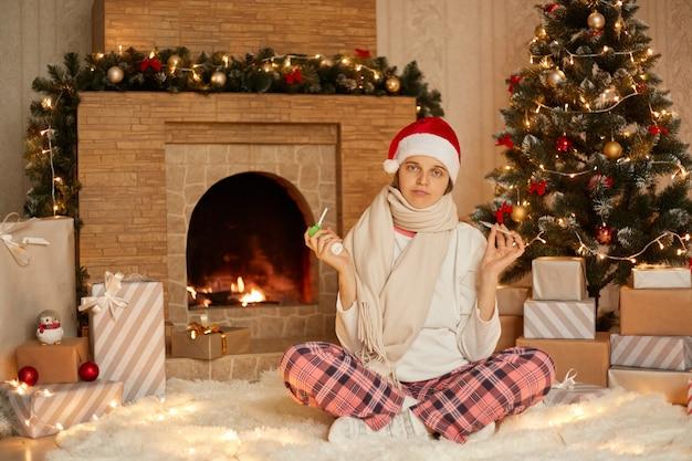 Młoda zdenerwowana kobieta siedząca nad kominkiem, ubrana w świąteczną czapkę i kraciaste spodnie, wyglądająca na chorą, trzymająca w rękach termometr i spray do gardła, siedzi na podłodze na miękkim dywanie ze skrzyżowanymi nogami.