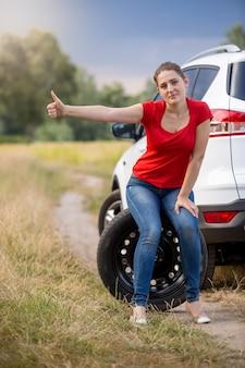 Młoda zdenerwowana kobieta siedzi na kole zapasowym w zepsutym samochodzie i jedzie autostopem