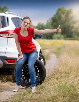 Młoda zdenerwowana kobieta siedzi przy zepsutym samochodzie i jedzie autostopem