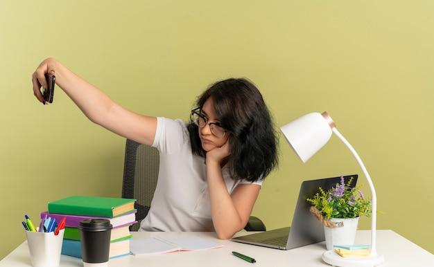 Młoda zdenerwowana ładna kaukaska uczennica w okularach siedzi przy biurku ze szkolnymi narzędziami patrzy na telefon robi selfie na zielonej przestrzeni z miejscem na kopię