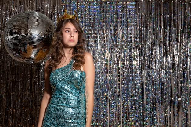 Młoda zdenerwowana piękna pani ubrana w niebiesko-zieloną błyszczącą sukienkę z cekinami z koroną na imprezie