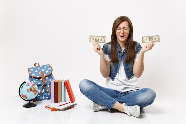 Młoda zdenerwowana studentka płacze trzymając banknoty dolarowe pieniądze w gotówce ma problem finansowy siedzieć w pobliżu globu, plecak szkolnych podręczników na białym tle