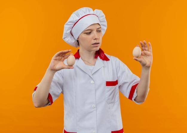 Młoda zdezorientowana blondynka kobieta kucharz w mundurze szefa kuchni trzyma jajka na białym tle na pomarańczowej ścianie