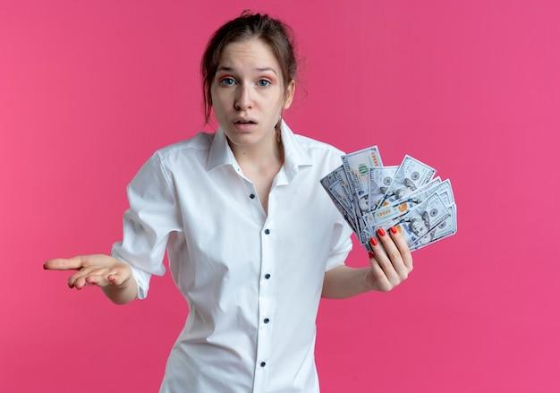 Młoda zdezorientowana blondynka rosjanka trzyma pieniądze i trzyma rękę otwartą