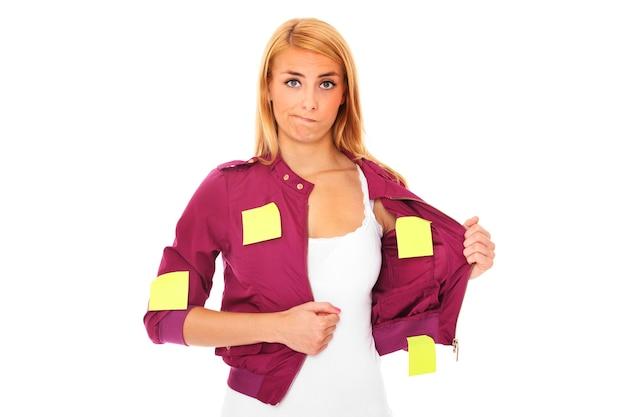 Młoda zdezorientowana kobieta z karteczkami samoprzylepnymi na całym ciele