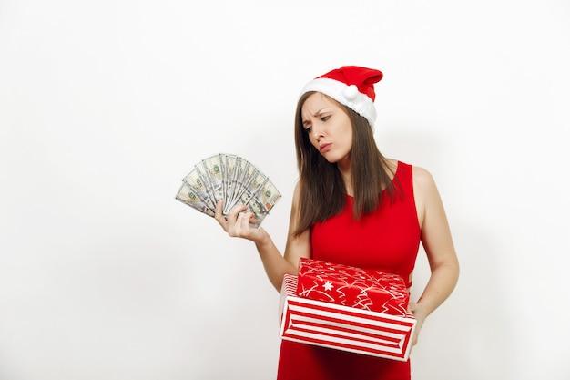Młoda zdezorientowana sfrustrowana kobieta w czerwonej sukience i boże narodzenie kapelusz trzymając pudełka i banknoty pieniądze na białym tle. santa dziewczyna z teraźniejszością i gotówką odizolowywającą. koncepcja wakacje nowy rok 2018.