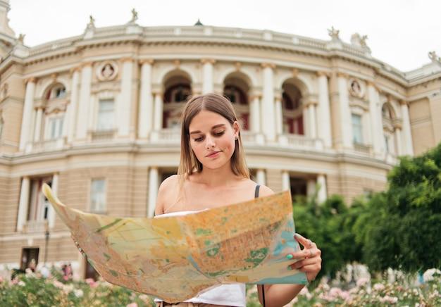 Młoda, zdezorientowana turystka trzyma w rękach mapę miasta na tle architektury turystycznego miasta.