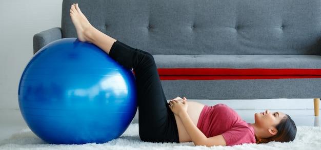 Młoda zdrowa azjatycka kobieta w ciąży leżąca i dotykająca brzucha położyła stopy na piłce do pilates podczas ćwiczeń w domu. koncepcja treningu ciąży.