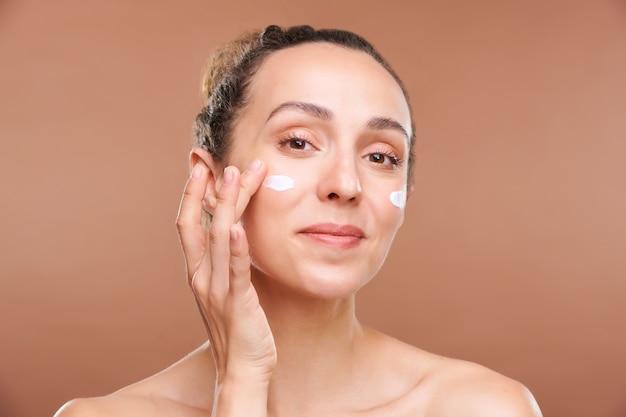Młoda zdrowa brunetka kobieta patrzy na ciebie podczas pielęgnacji twarzy i stosowania kremu odmładzającego po usunięciu makijażu