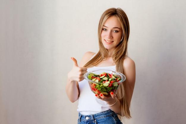 Młoda zdrowa dziewczyna z puchar sałatki warzywnej