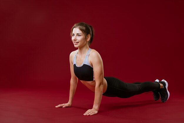 Młoda zdrowa kaukaska kobieta w odzieży sportowej na czerwonym tle zajmuje się fitnessem