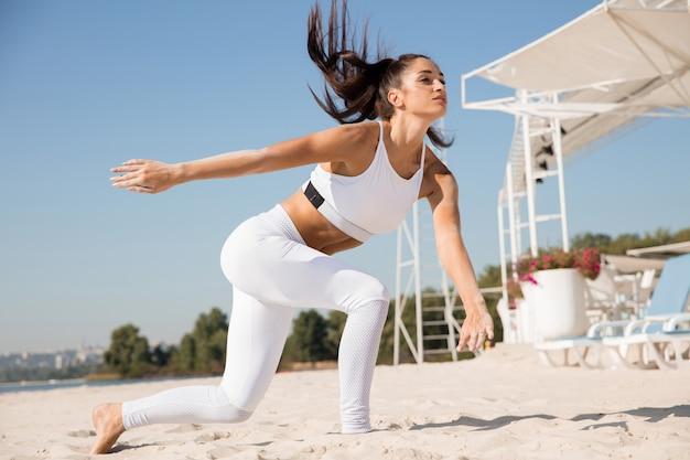 Młoda zdrowa kobieta bieganie i robienie rzuca się na plaży.