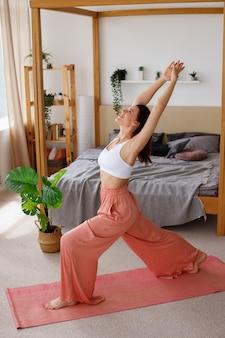 Młoda zdrowa kobieta jest joga rano w domu.