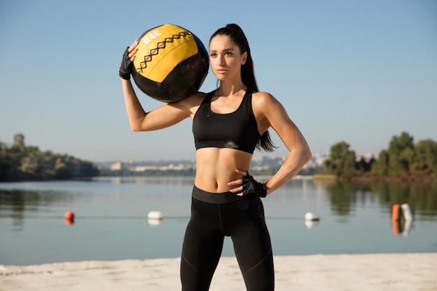 Młoda zdrowa kobieta pozuje pewnie z piłką na plaży.