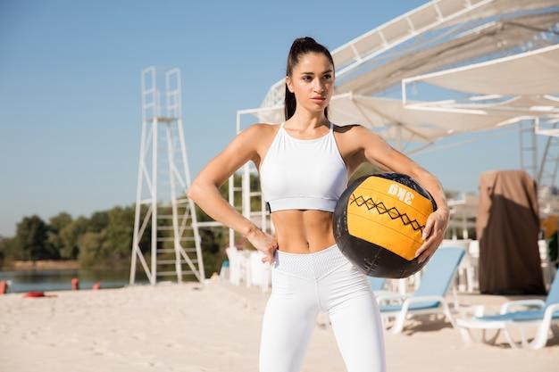 Młoda zdrowa kobieta pozuje z piłką na plaży.