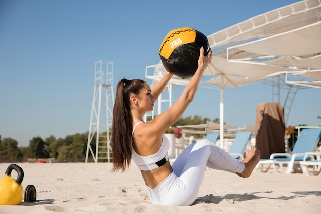 Młoda zdrowa kobieta robi brzuszki z piłką na plaży.