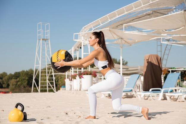Młoda zdrowa kobieta robi przysiady z piłką na plaży.