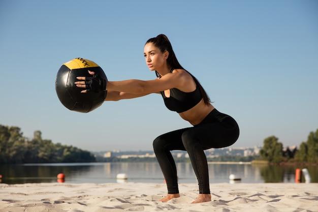 Młoda zdrowa kobieta robi przysiady z piłką na plaży